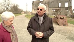 Robert Hébras y Palmira Dessaix, miembro del Ateneo Republicano du Limousin, frente al lugar donde todos los vecinos fueron reunidos en 1944 el día de la masacre.